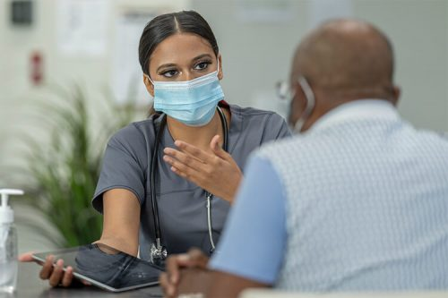 nurse practitioner wearing face mask consults with patient