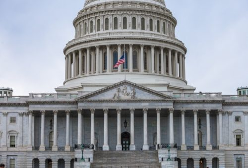 The U.S. Capitol building's east facade is shown with the U.S. flag flying in front of it.