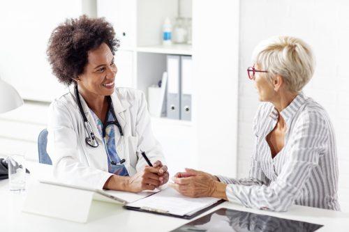 A caregiver discusses treatment with a patient