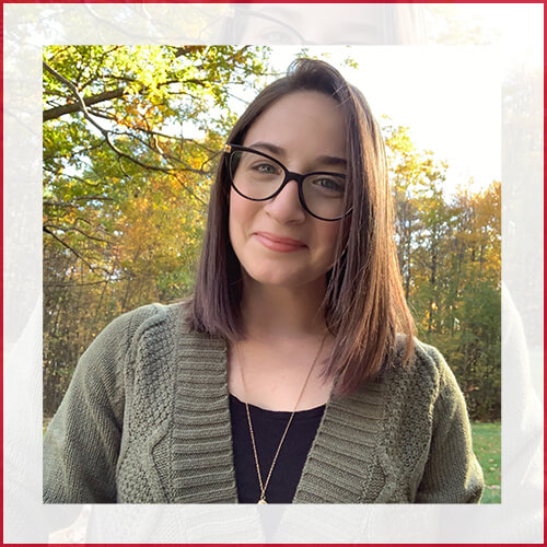 Stephanie Marchetti headshot in green sweater in front of trees