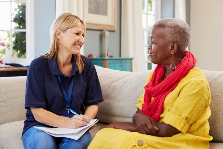 A case management assistant meets with a senior woman in their home.