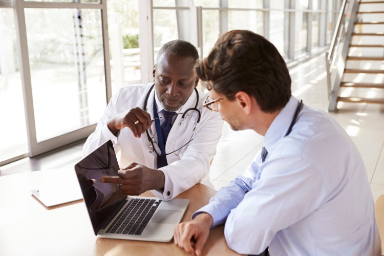 A medical sales rep shares a presentation with a doctor on a laptop