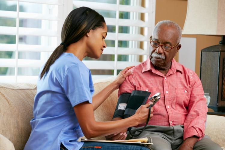 A patient care assistant measures a patient's blood pressure
