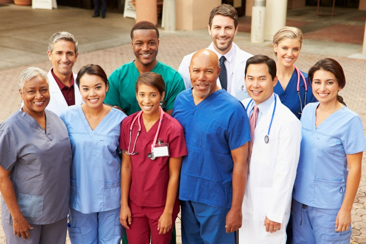 Smiling medical staff stand outside a hospital