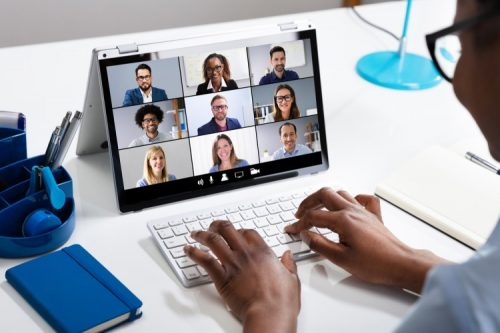 A manager leads a remote team meeting on their laptop.