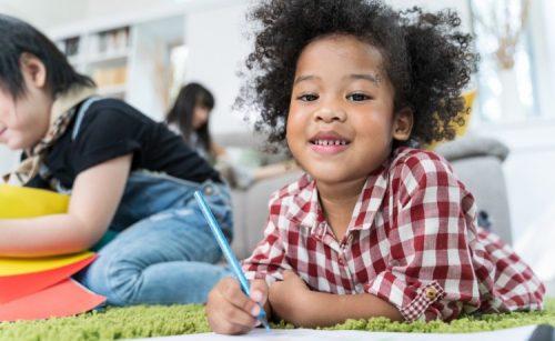 A preschool child draws with a colored pencil in a classroom