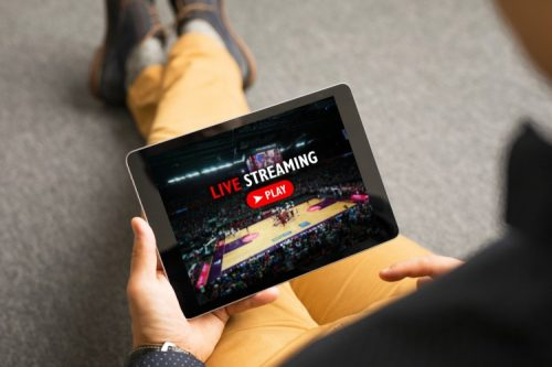 A man watching a basketball game streaming live on a tablet.