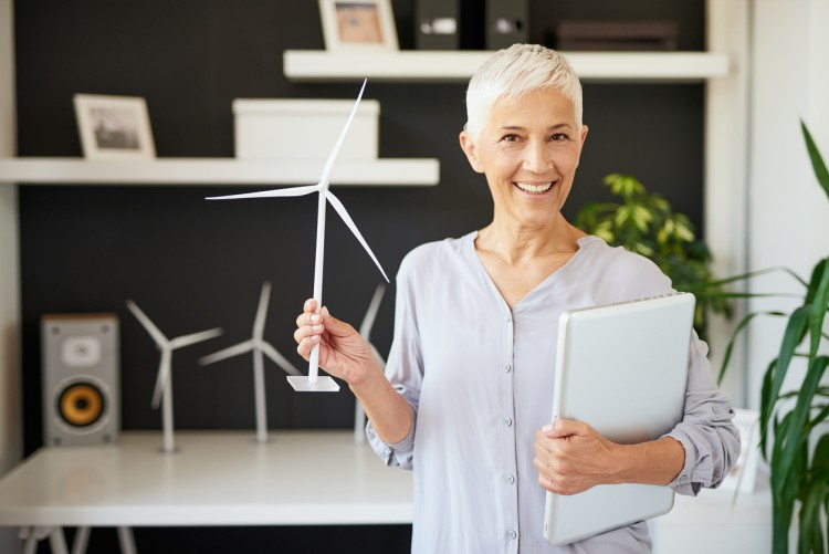 A businessperson displays a model of a windmill used to reduce a company's carbon footprint.
