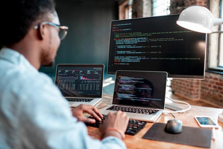 man looking at three computer screens with code