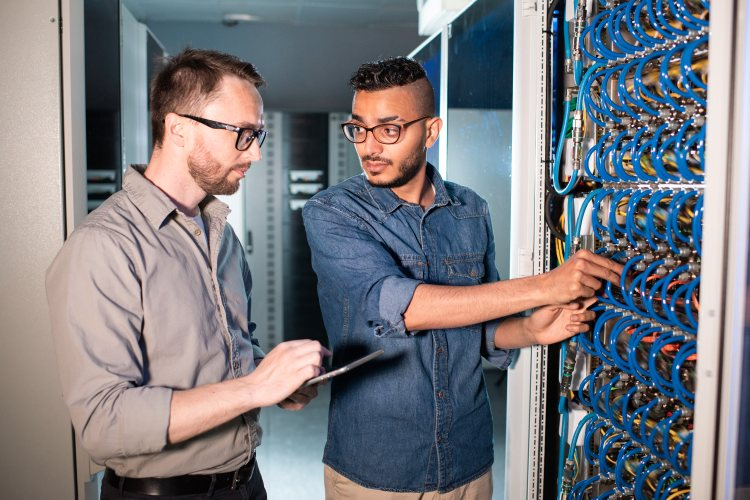 Two computer support specialists in a data center