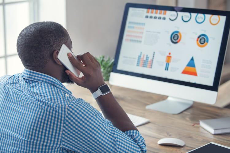 A statistician analyzes data on a desktop computer.