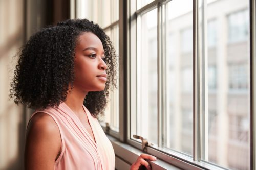 woman contemplates while looking out window