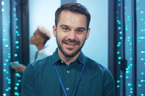 Smiling man standing in server room