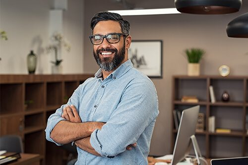 Smiling man standing in modern office