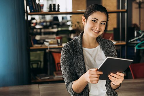 Smiling woman holding tablet in open office