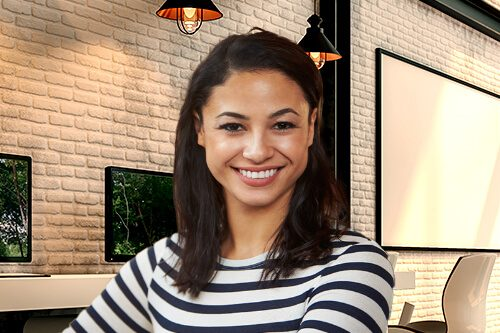 Smiling woman sitting in front of computer in modern office