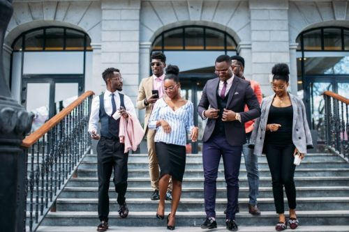 A group of Black professionals walking out of an office building.