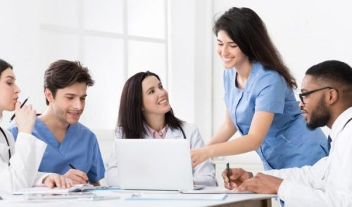 Five nursing students gather around a laptop at a work table.
