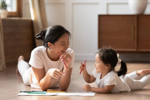 A smiling mother and daughter lying on the floor and drawing with colored pencils.
