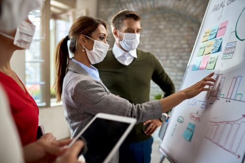 Three colleagues wearing face masks are brainstorming while gathered at an office whiteboard.
