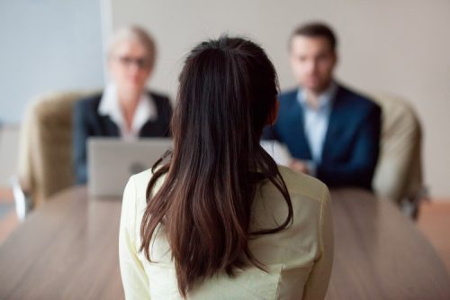 a female employee faces a review board