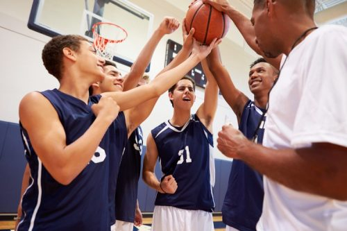 A basketball coach celebrates with players
