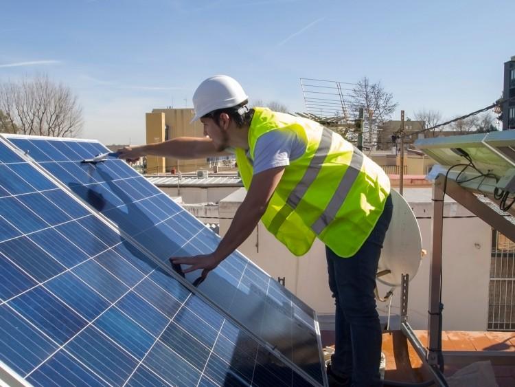 A technician cleans solar panels.