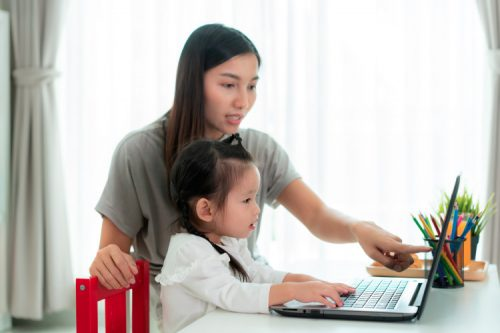 A parent and child engage in online learning on a computer.