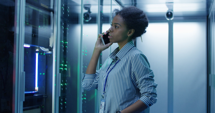 A networker administrator speaks on a cellphone in a server room.