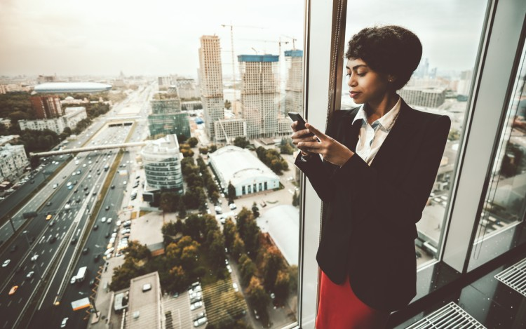 A business executive standing by a window in her office building looking at her smartphone.