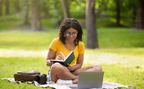 A college student doing homework in the park.