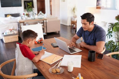 A parent and child study together at a table.