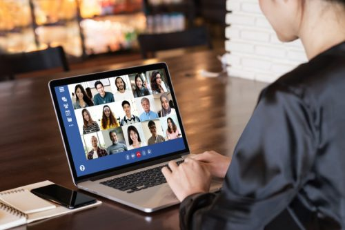 A change manager works with a remote team on a laptop.
