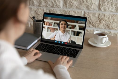 An employee and manager conduct a performance review via video conference.