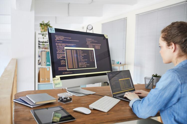 An algorithm developer works on multiple screens at a workstation.