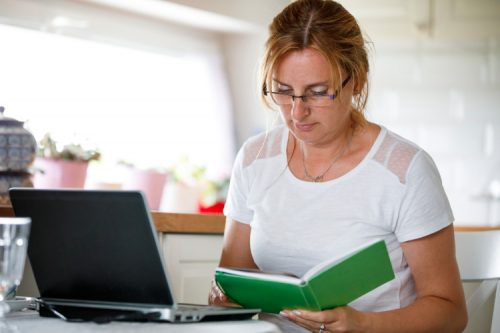 An adult student with a laptop and planner.
