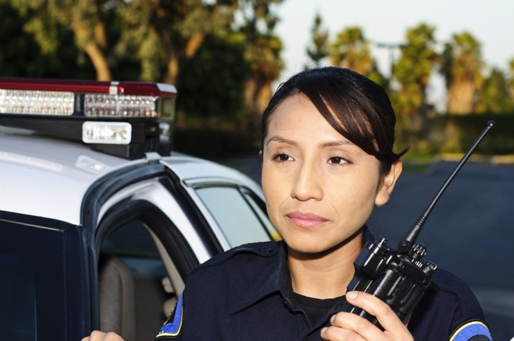 A police officer standing beside a patrol car and holding a hand-held radio.