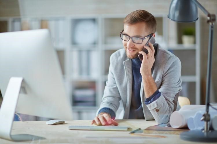 A social work case manager makes a phone call at his desk.