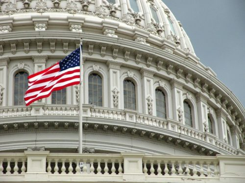 The American flag waving in front of the U.S. Capitol.