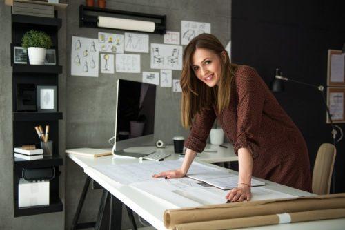 A smiling entrepreneur reviews plans at a desk.