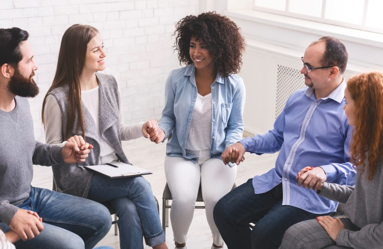A drug and alcohol treatment specialist is holding hands with a circle of members during a group therapy session