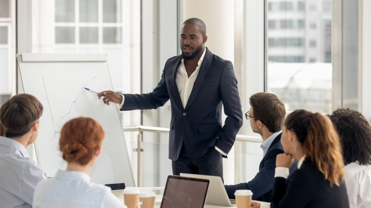 A CFO is giving a presentation to a finance team while standing at a flipchart.
