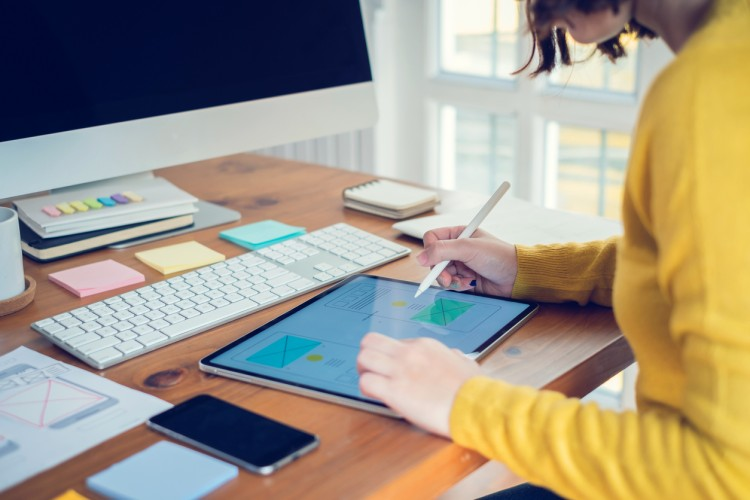 A digital artist designs a user interface using a tablet and stylus.