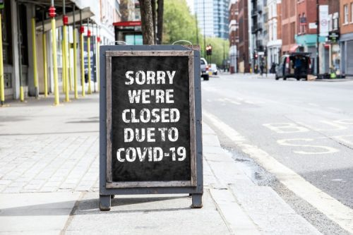 A sign outside a business announces it is closed because of COVID-19.