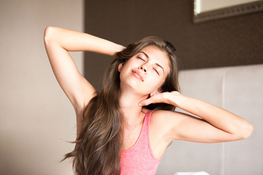 beautiful happy young long haired woman waking up in the morning