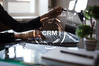 Image of person pointing towards a laptop screen with CRM watermark over the image