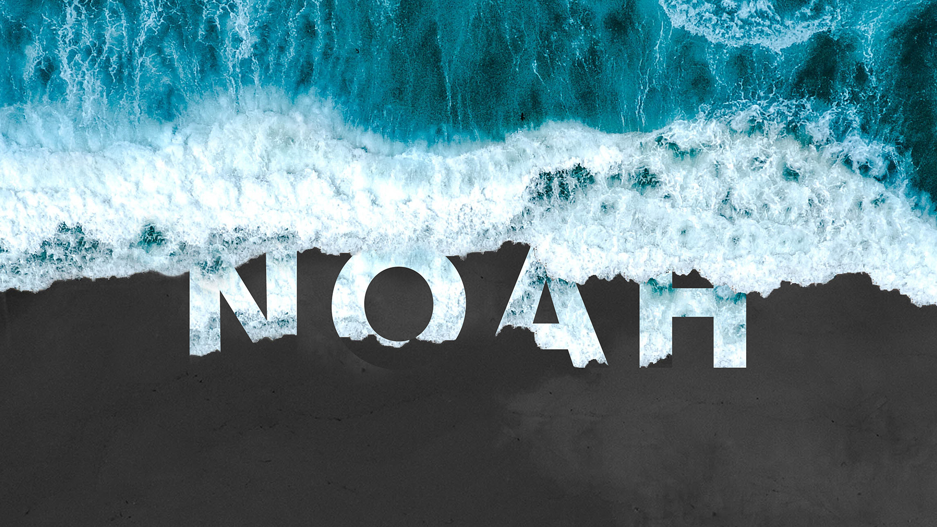 Ocean waves with Noah written on the sand.