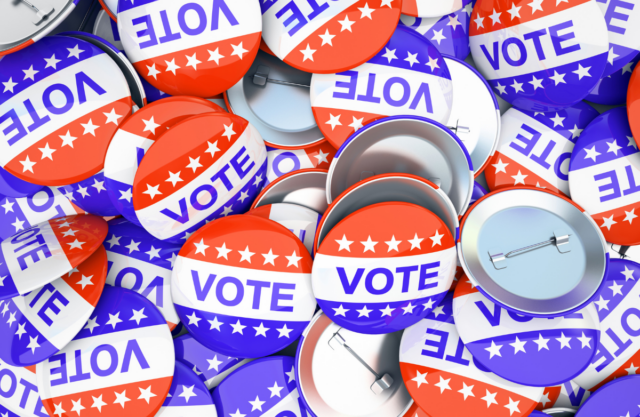 Photo of a pile of buttons that read VOTE