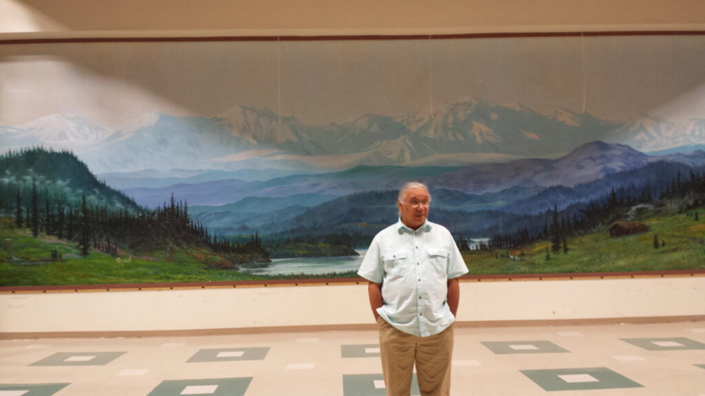 Photo of a man standing in front a mural of a mountain