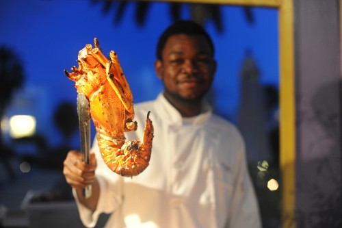A Caribbean chef holding a giant shrimp